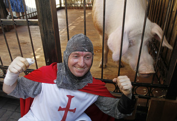 A fan of England poses for pictures in front of the cage of Funtik, the pig which predicts the result of the Euro 2012 soccer matches, in the fan zone in Kiev