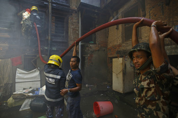 Members of the search and rescue team work alongside with locals to put out flames after houses caught fire in Kathmandu