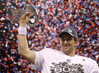 New York Giants quarterback Eli Manning holds the Vince Lombardi Trophy after defeating the New England Patriots