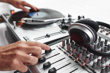 a person playing records and using a mixing board