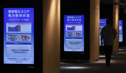 Man walks past electronic monitors displaying current electricity usage status in TEPCO's supply area at Tokyo railway station