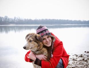 Young woman kneeling embracing dog