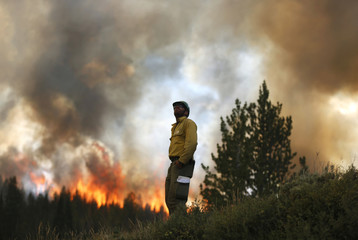 Firefighter Alex Abols monitors fire on the north flank of the Fontenelle Fire outside Big Piney, Wyoming