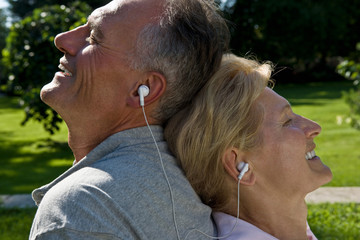 Man and woman listening to earphones