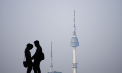 A couple is silhouetted against the backdrop of N Seoul Tower, commonly known as Namsan Tower, in Seoul