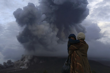 A mother holds her son as they watch the eruption of Mount Sinabung at Berastepu village in Karo district, Indonesia's North Sumatra province