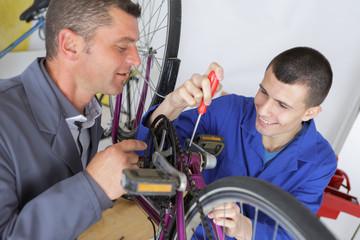 teacher and apprentice fixing a bike