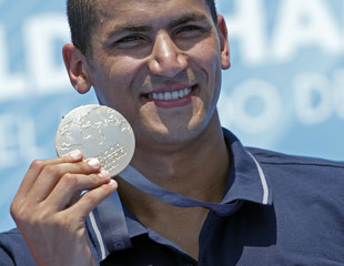 Winner Mellouli of Tunisia holds his gold medal after the men's 5km open water race at the World Swimming Championships in Barcelona