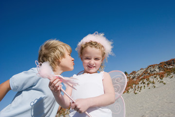 Girl wearing costume with boy on beach
