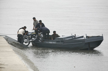 North Koreans are seen loading a Chinese-made motorcycle onto a boat on the banks of the Yalu River in the city of Dandong in northern China
