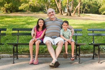 Grandfather sitting with grandchildren in park, portrait