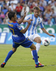Malaga's Monreal and Levante's Venta fight for the ball during their Spanish first division soccer match at the Ciudad de Valencia Stadium in Valencia