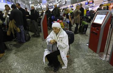 An elderly woman waits at Budapest International Airport
