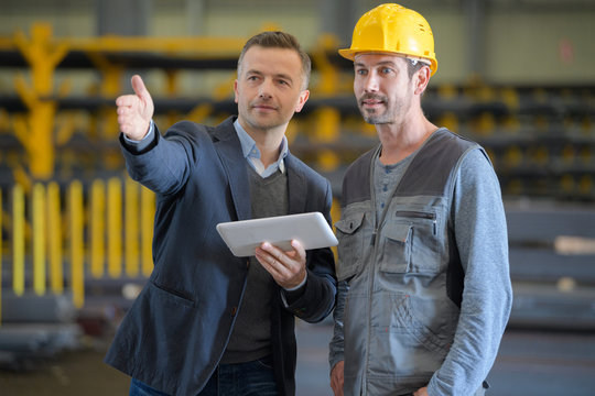 businessman talking to working man in factory