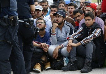 Migrants wait to cross the border from Austria to Germany near Freilassing