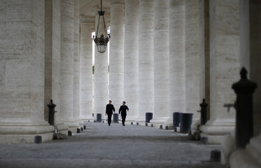 Priests walk through the colonnade of Saint Peter's Square at the Vatican