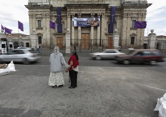 Two women stand and pray in front of a Cathedral after the announcement of the newly elected Pope Francis in Guatemala City