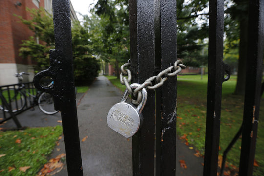 A gate to Harvard Yard is chained and locked shut at Harvard University in Cambridge