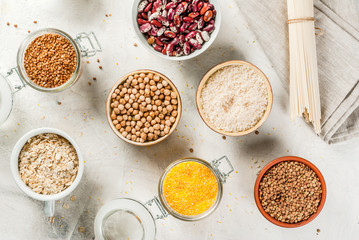 Selection of gluten-free products, cereals: xanthan gum. buckwheat,Rice, rice noodles, chickpeas, lentils, corn, beans, oatmeal. In bowls and jars, the top view on white table top view copy space