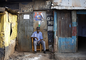 A supporter of Kenyan PM Odinga sits in front of a poster outside his house as he waits for election results in Nairobi