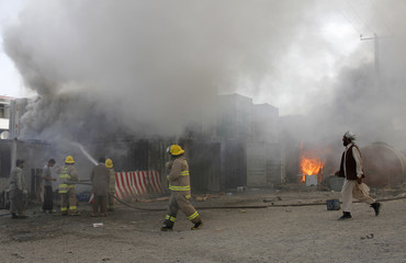 Afghan firefighters extinguish a fire at a building set ablaze by protesters during a demonstration in Kabul