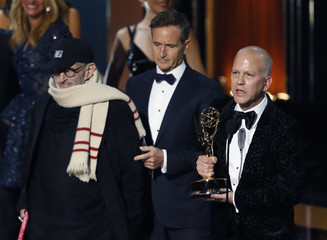 """Executive producer Ryan Murphy accepts the award for Outstanding Television Movie for """"The Normal Heart"""" as playwright Larry Kramer listens onstage during the 66th Primetime Emmy Awards in Los Angeles"""