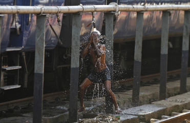 A man baths using a pipe that supplies water to trains at a railway station in Chennai