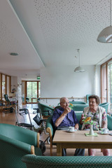 Man and woman, both seniors, couple, sitting on couch in retirement home having coffee