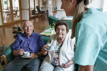 Nurse serving coffee to senior man and woman in retirement home