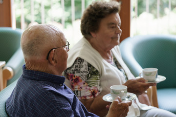 Senior couple having cup of coffee while chatting in nursing home