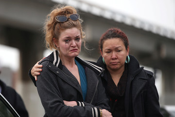 Twiggy Damy hugs an unidentified mourner at a sidewalk memorial near the burned warehouse following the fatal fire in the Fruitvale district of Oakland