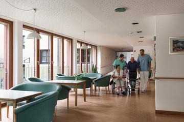 Nurses pushing senior man and woman in wheelchair trough the hall of nursing home