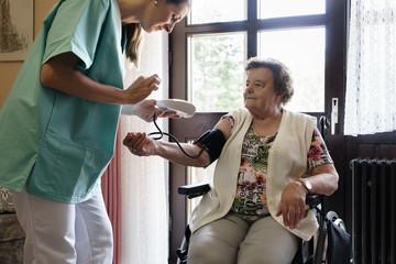 Nurse measuring blood pressure of senior woman in elderly care home
