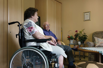 Two seniors sitting in their room in rest home chatting about the good old times