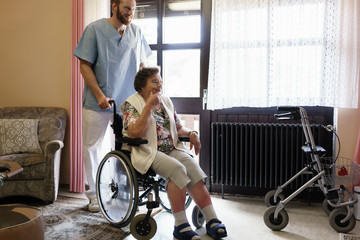 Elderly woman in wheelchair being helped by nurse getting out or her room in nursing home