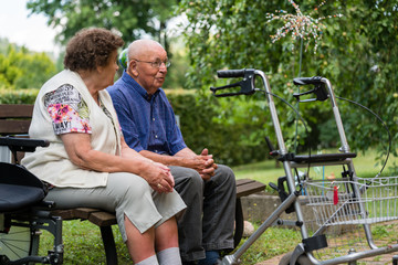 Senior man and woman in retirement home sitting on a bench in park
