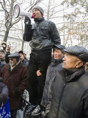 An opposition protester, balancing on a garden fence, uses a loudspeaker during a rally in Almaty