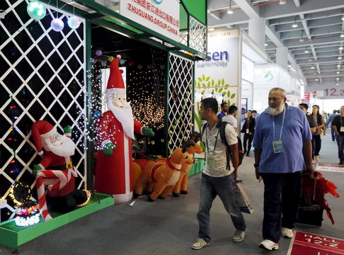 Men walk past a booth displaying Christmas lights decorated with Santa Claus dolls at Canton Fair in the southern Chinese city of Guangzhou