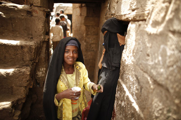 A girl from the Akhdam community stands outside her family's house in a slum area in Sanaa