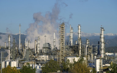 An oil refinery is seen with the Rocky Mountains freshly covered with snow in the background in Denver