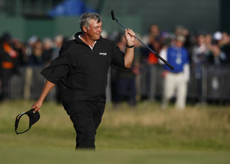 Darren Clarke of Northern Ireland gestures as he walks up the fairway during the third round of the British Open golf championship at Royal St George's in Sandwich