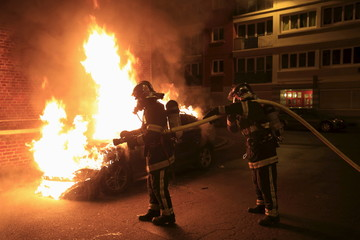 Firefighters extinguish a burning car following New Year celebrations in Lille, northern France