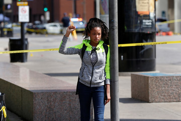 Dajia Dominguez,14, from Dallas, stands with her fist up at Rosa Parks Plaza near the shooting scene in Dallas, Texas