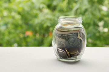 Glass jar with money and coins against background of greenery