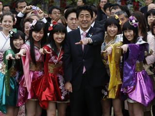 Japan's PM Abe poses with Japanese idol group Momoiro Clover Z at a cherry blossom viewing party at Tokyo's Shinjuku Gyoen park