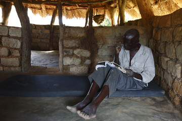 HIV-positive 71-year-old Hachiploa reads in his thatched hut during a visit by a home-based care team in the village of Nedwmba, south of the Chikuni Mission in the south of Zambia