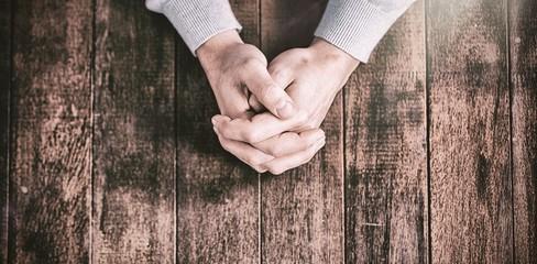 Cropped hands of man praying