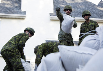 Canadian Armed Forces soldiers pile sand bags from the rising Bow River in Calgary