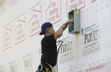 Construction worker Marco Bueno works on an electrical box on a new home in Matthews