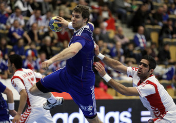France's Accambray attempts to score next to Bahrain's Merza during their group A match at the Men's Handball World Championship in Lund